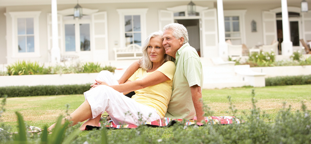 A mature couple sits on a blanket in front of a house
